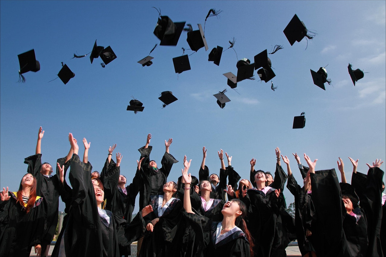 Group of students throwing graduation hats in the air