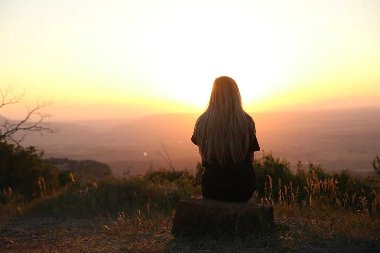 Woman looking at the beautiful sunrise on top of a hill