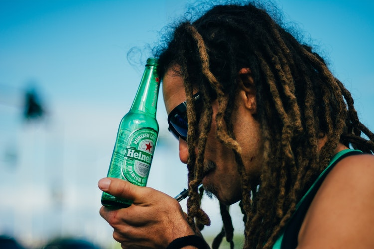 Rastaman lighting up a joint and holding a beer