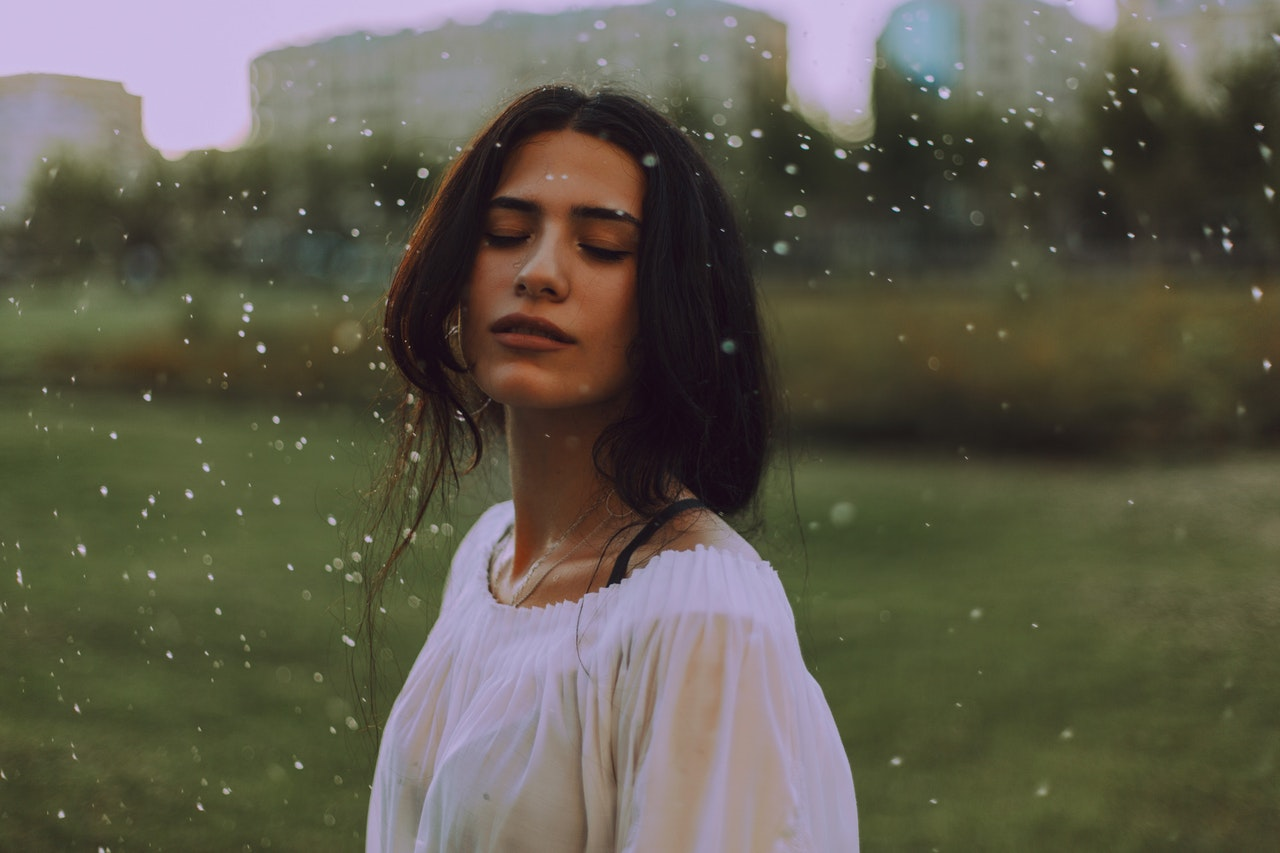 Woman standing in rain that washes away the negative