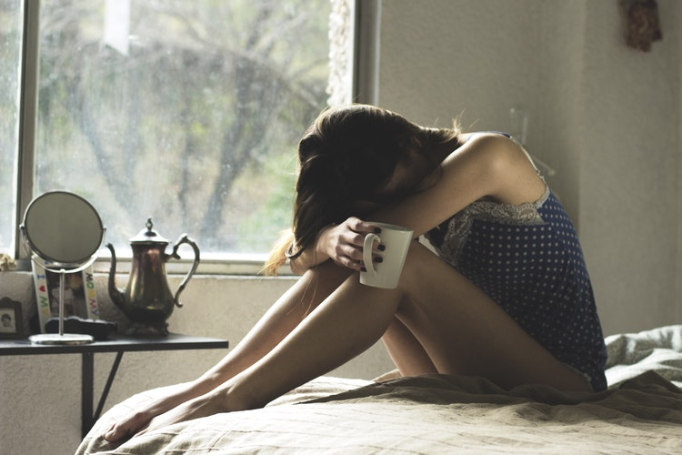 Depressed woman sitting on the bed while holding coffee mug with head held down