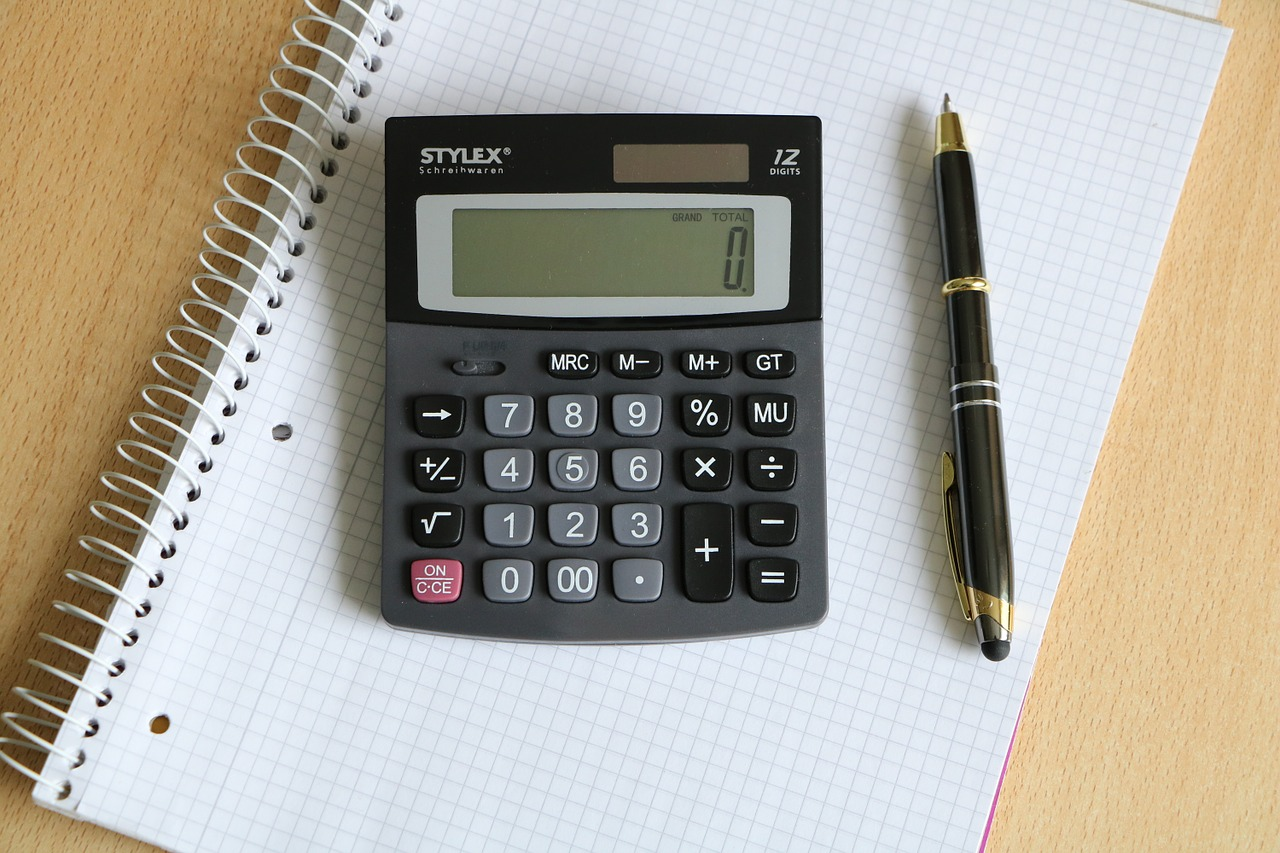 Old-school calculator on a piece of paper next to a pen